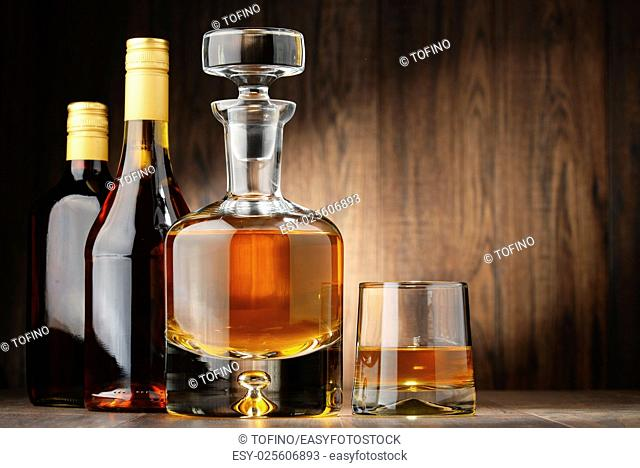Composition with bottles of assorted alcoholic beverages and glass of whisky