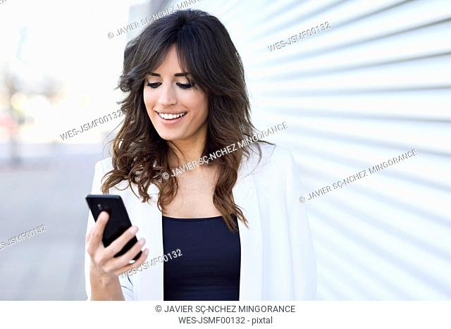Portrait of smiling businesswoman looking at cell phone
