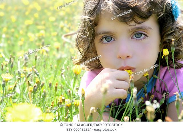 Adorable little girl smell flower in the country meadow