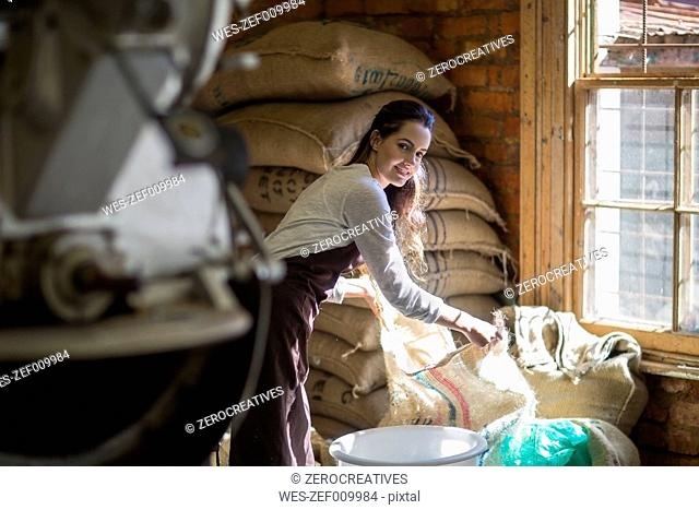 Young woman roasting coffee beans