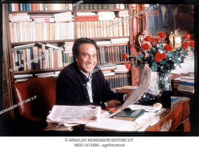 Emilio Fede in his office . The anchorman Emilio Fede is smiling and holding a newspaper while seated at the desk of his office; behind him a bookcase
