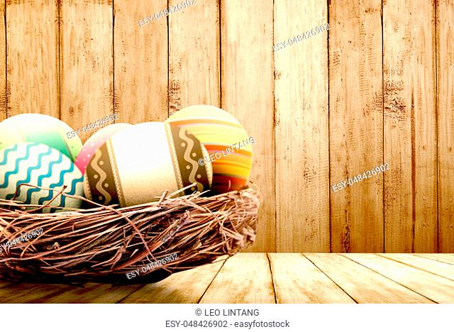 Colorful easter eggs in the nest on wooden table with wooden wall background. Happy Easter