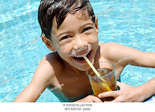 Boy drinking iced tea in pool