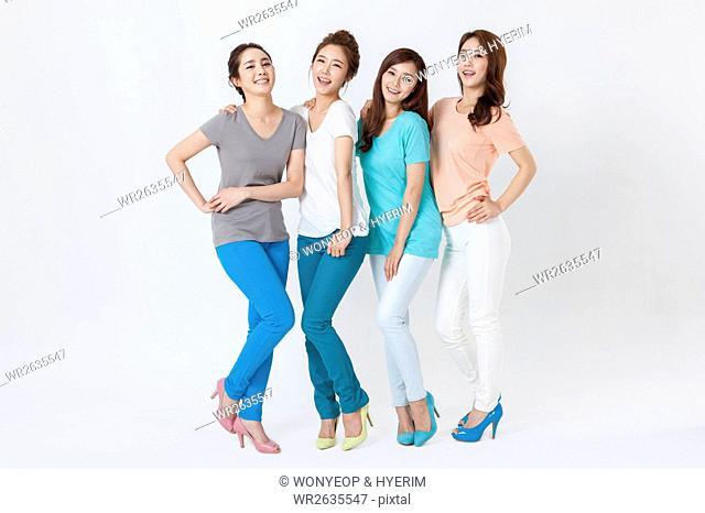 Four young smiling women standing posing
