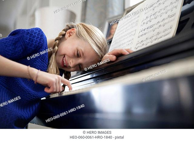 Happy young girl playing piano at home