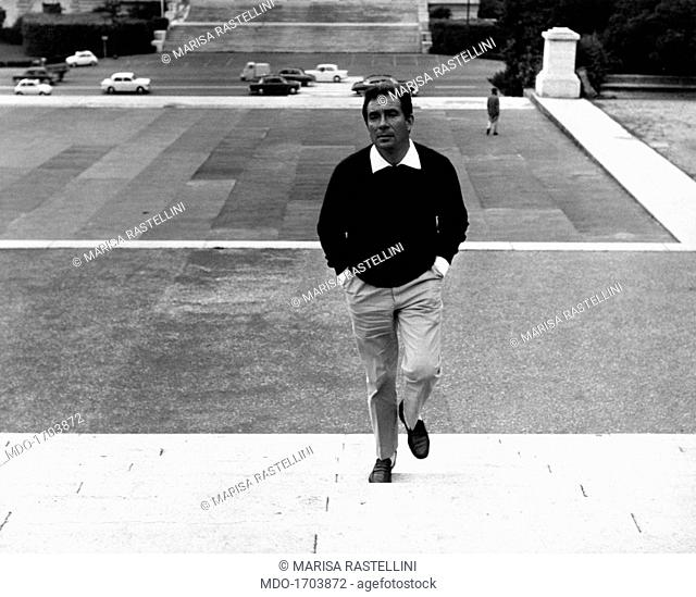 Ugo Tognazzi going up the stairs of a square. The Italian actor Ugo Tognazzi goes up the stairs of a square in Villa Borghese; in his latest movies