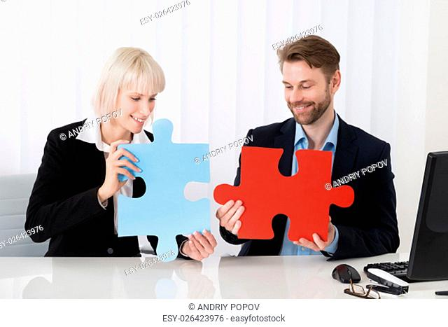 Two Young Happy Businesspeople Holding Puzzle Pieces At Desk