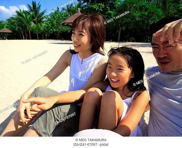 Mid adult couple sitting on the beach with their daughter