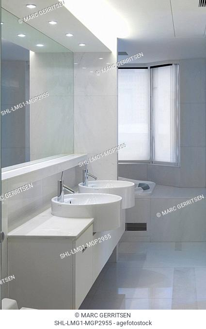Double bowl sinks in white bathroom