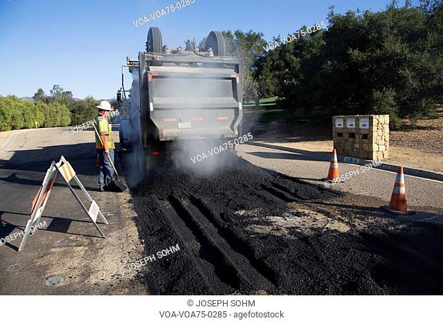 Roadworker repaves road with steam, Encino Drive, Oak View, California, USA