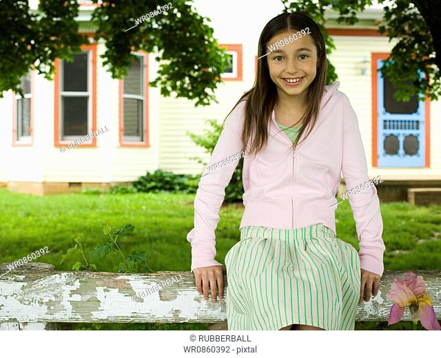 Portrait of a girl sitting on a wooden fence