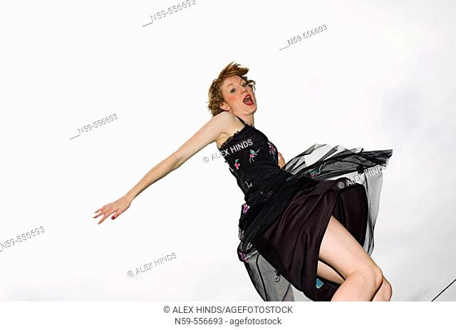 Girl in party dress jumping with excitement