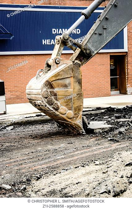 Specific image of a bucket on a backhoe excavating machine being used to remove asphelt from a road