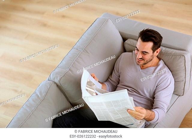 Upper view of man reading newspaper in sofa