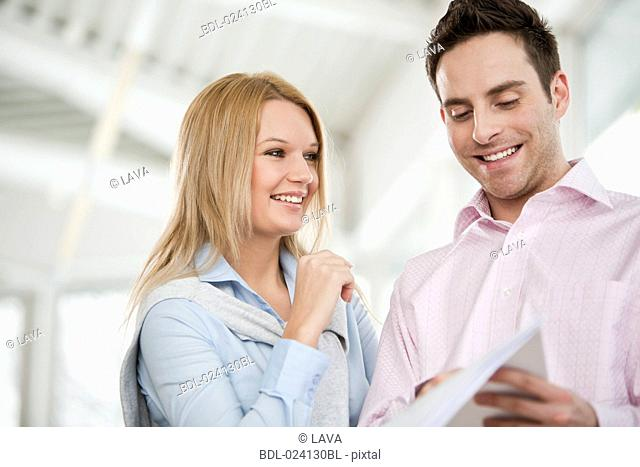 portrait of businessman and female colleague reading document