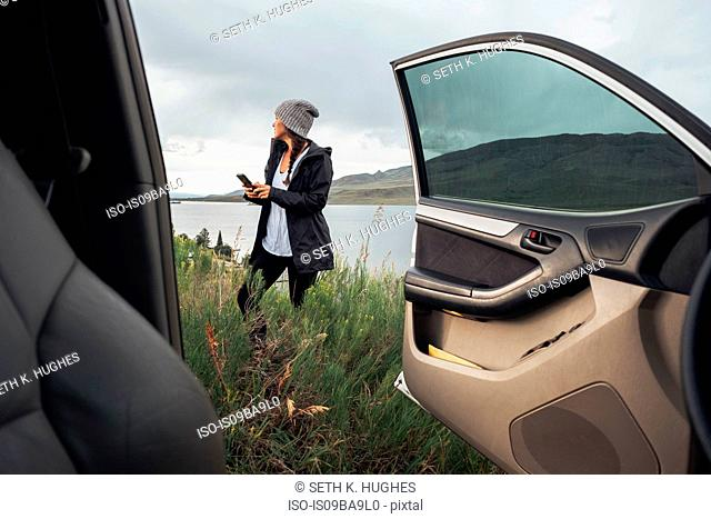 Young woman standing beside Dillon Reservoir, holding smartphone, view through parked car, Silverthorne, Colorado, USA