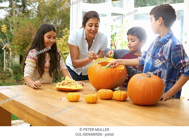 Mother and children carving pumpkin in dining room