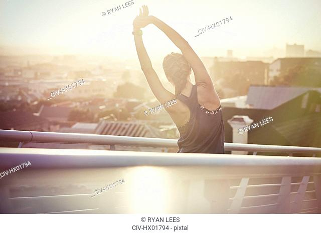 Female runner stretching arms on urban footbridge at sunrise