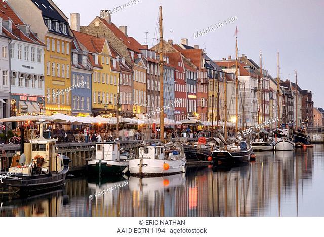 Boats and side-walk cafes along the Nyhavn canal in Copenhagen Denmark