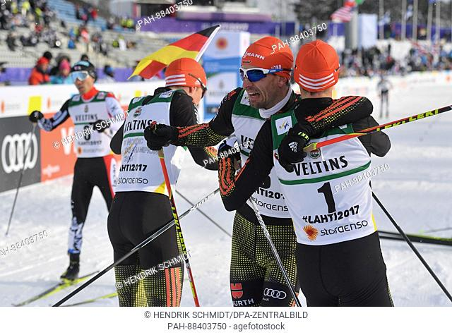 Johannes Rydzek (2nd l, 1st Place), Eric Frenzel (r, 2nd Place) and Bjoern Kircheisen (l, 3rd Place), all from Germany, celebrate after the single combination...
