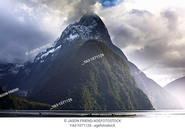 New Zealand, Southland, Fiordland National Park  A clearing storm behind Mitre peak, a famous landmark of the Milford Sound