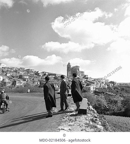 Three Italian men standing in the street leading to the neighbourhood called Ragusa Ibla on the top of a hill. Ragusa, 1955