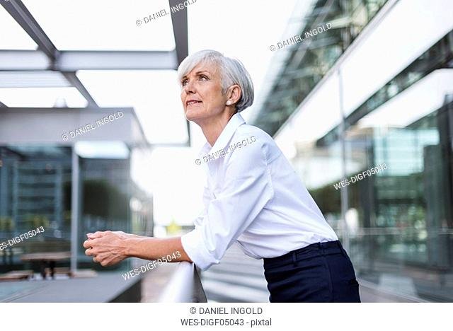 Senior woman leaning on railing in the city looking up