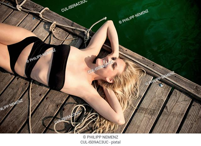 Young woman sunbathing on pier