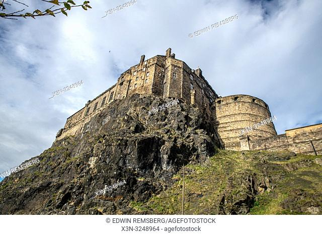 Looking up at the historic fortress of Edinburgh Castle sitting on the edge of a rocky cliff, Edinburgh, Scotland