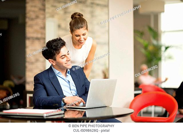 Businessman and woman looking at laptop in office