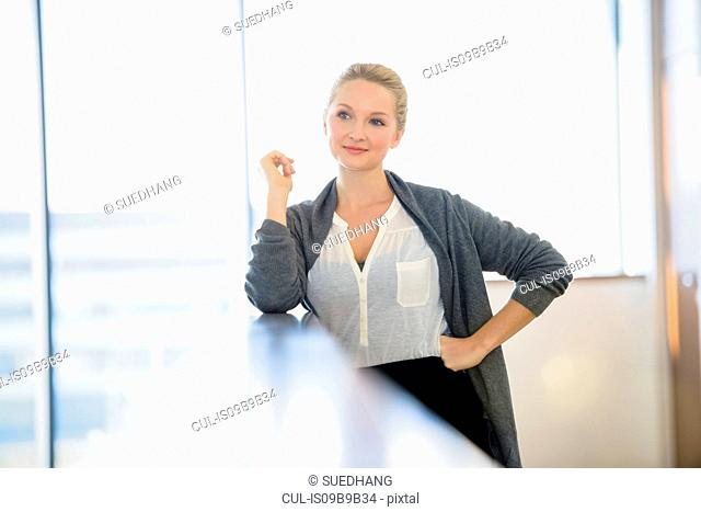 Confident young businesswoman with hand on hip in office corridor