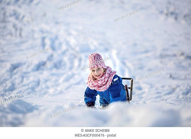Portrait of smiling girl girl with sledge in the snow
