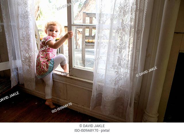 Child climbing over opened window