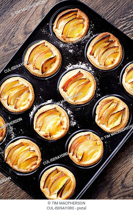 Overhead view of miniature frangipane apple tarts in baking tray