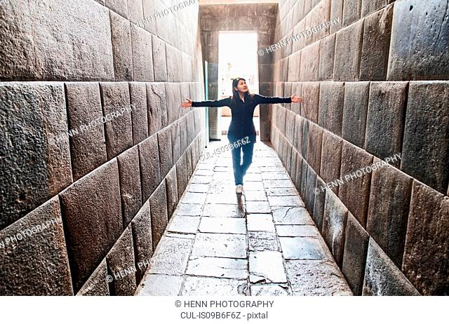 Woman stretching her arms between ancient Inca walls, Cusco, Peru, South America