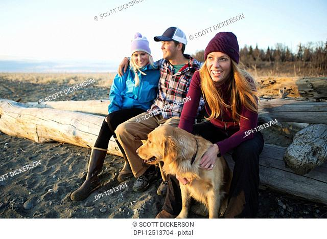 A young couple and a friend with a dog sit on a piece of driftwood on a beach looking out to the ocean at sunset; Anchorage, Alaska, United States of America