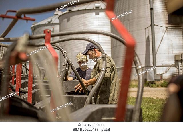 Caucasian farmer explaining machinery to son on farm