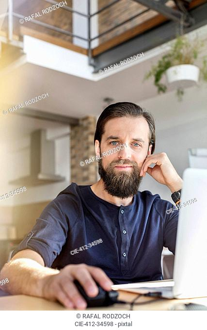 Portrait confident male design professional working at laptop in office