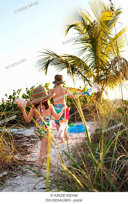 Girl and brother gathering seashells at beach, Sanibel, Florida, USA