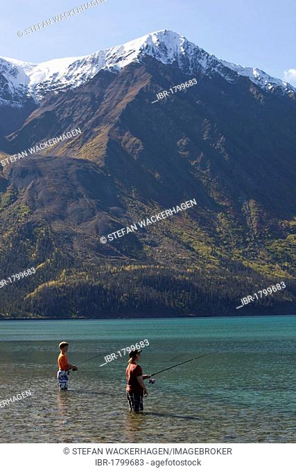 Children, young boys, standing in shallow water, fishing at Kathleen Lake, King's Throne behind, St. Elias Mountains, Kluane National Park and Reserve