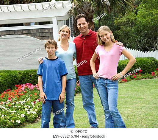 Caucasian family of four posing for portrait in yard