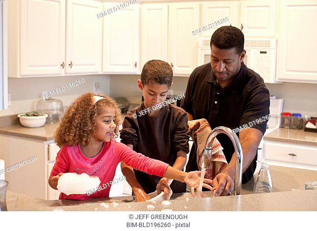 Family washing dishes together
