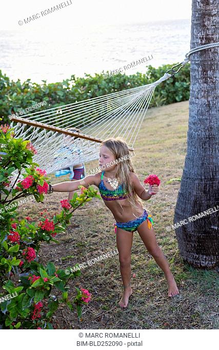 Caucasian girl wearing a bikini picking flowers