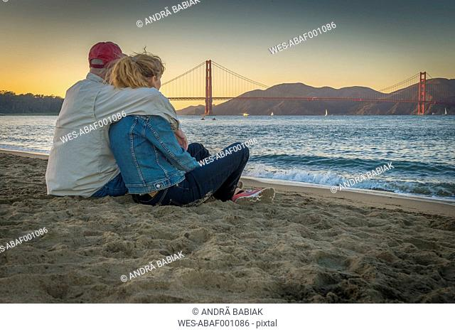 USA, California, San Francisco, Mature couple sitting at the beach at the Golden Gate Bridge at twilight