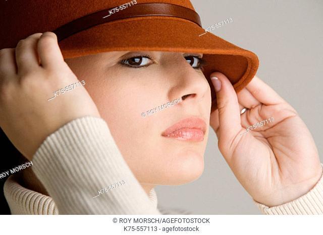 Portrait of caucasian-hispanic woman in her twenties with a hat