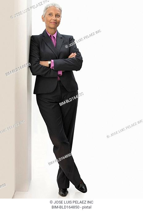 Mixed race businesswoman leaning on wall