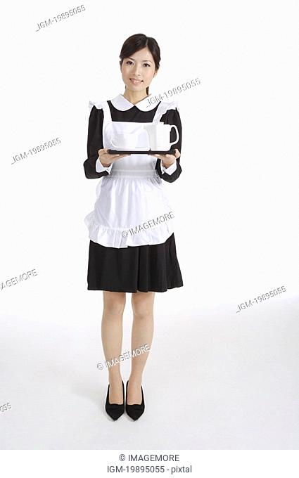 Young waitress holding a tray with teapot and teacup