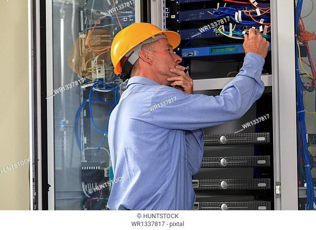 Electrical engineer working with switches and servers in broadband communication hub of electric power plant