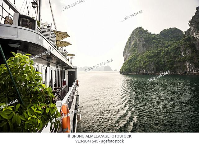 A tourists vessel in the karst landscape of Ha Long Bay, Quang Ninh Province, Vietnam. Ha Long Bay is a UNESCO World Heritage Site