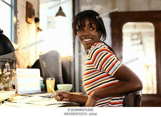 Portrait of smiling young woman sitting at desk in a loft
